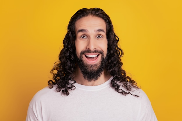 Portret van funky verbaasde positieve man kijkt camera open mond op gele achtergrond