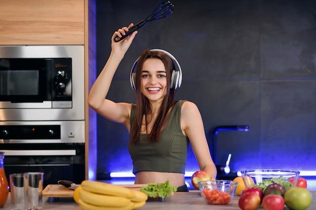 Portret van funky vrolijke huisvrouw stel je voor dat ze pop start, luister naar muziek op haar headset, houd keukengerei, zing favoriete liedje tijdens het koken, avondmaal, smakelijke lunch in het witte huis