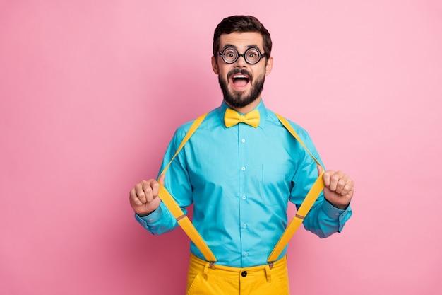 Portret van funky vrolijke kerel bretels met plezier trekken