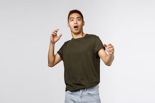 Portret van gealarmeerde en bang, geschokte aziatische man hijgend, stap achteruit en hief zijn handen angstig op, geschrokken starend naar iets beangstigend, staand in ontzag over de grijze muur