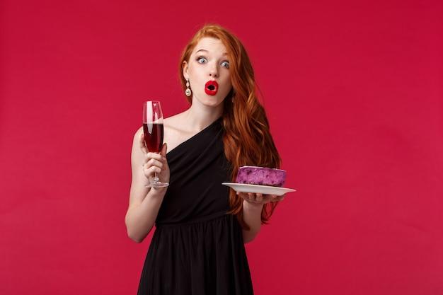 Portret van geamuseerd en afgevraagd, sprakeloze schattige roodharige vrouw in stijlvolle zwarte jurk, met glas champagne en cake, lippen vouwen verrast, rode muur staan