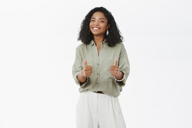 Portret van geamuseerd en vermaakt charismatische afro-amerikaanse vrouw met krullend kapsel duimen opdagen