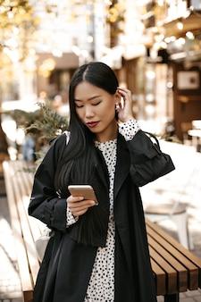 Portret van gebruinde aziatische vrouw in zwarte trenchcoat en witte stippenjurk staat buiten en chat aan de telefoon