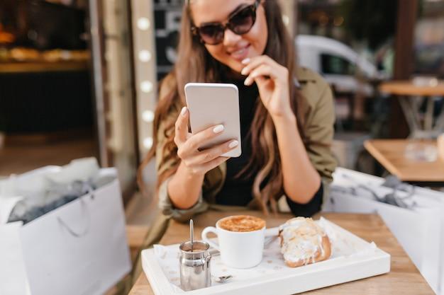 Portret van gebruinde dame met elegante manicure en kopje latte op voorgrond