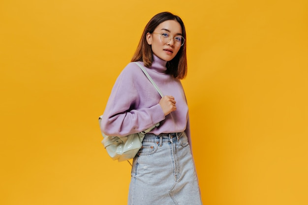 Portret van gebruinde kortharige jonge vrouw in brillen, spijkerrok en paarse trui kijkt naar voren en houdt mintrugzak op oranje muur