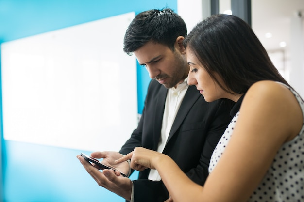 Portret van geconcentreerd zakenlui die mobiele telefoon met behulp van