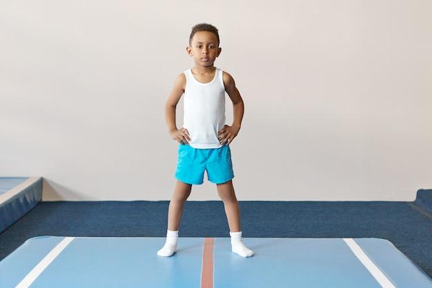 Portret van geconcentreerde donkere huid jongen gekleed in wit overhemd