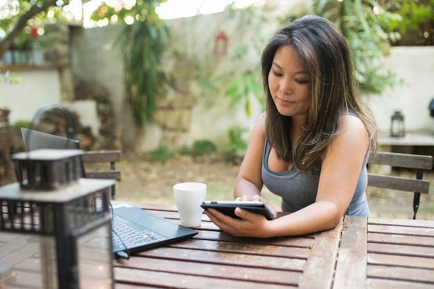 Portret van geconcentreerde japanse vrouw die tablet in openluchtcafé gebruikt. mooi meisje winkelen of online chatten, plezier maken, lezen, freelancer werken. koffie drinken