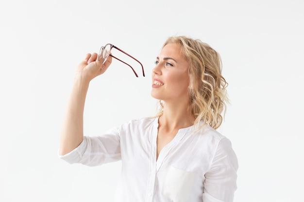 Portret van geconcentreerde mooie vrouw met slecht zicht wat betreft glazen geïsoleerd op een witte achtergrond.
