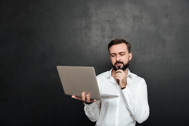 Portret van geconcentreerde ongeschoren kerel die zilveren laptop bekijkt en zijn kin raakt, die over donkergrijze muur wordt geïsoleerd