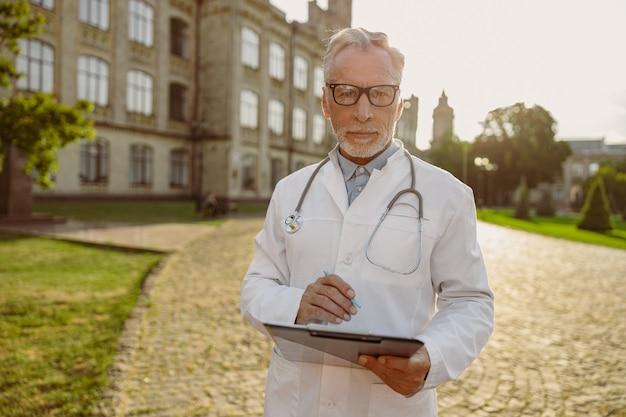 Portret van geconcentreerde senior mannelijke arts in laboratoriumjas en bril met klembord op zoek