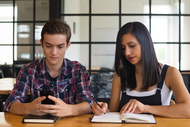 Portret van geconcentreerde studentenmeisje en jongenszitting bij bureau