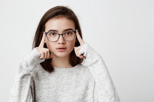 Portret van geconcentreerde tienervrouw met donker recht haar die oogglazen dragen die pensively kijken