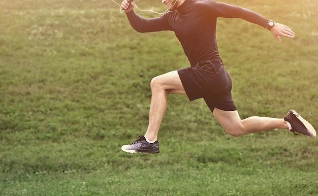Portret van geconcentreerde zelfverzekerde gespierde vol krachtsportman die korte broek en sneakers draagt.