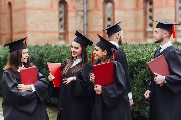 Portret van gediplomeerde schooljonge geitjes die zich met graadrol bevinden in campus op school