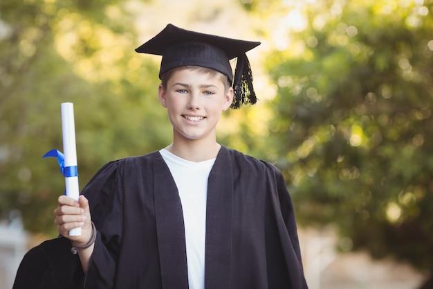 Portret van gediplomeerde schooljongen die zich met graadrol in campus bevindt