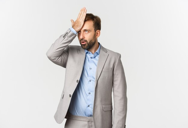 Portret van geërgerde mannelijke ondernemer in grijs pak