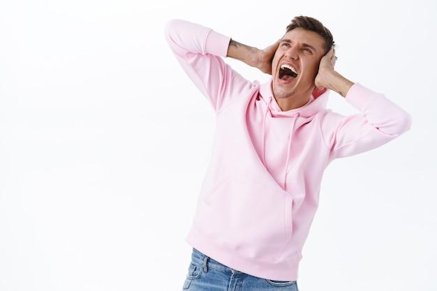 Portret van geërgerde pissige jongeman die in quarantaine zit tijdens de pandemie van het coronavirus, een hekel heeft aan persoon die boven woont, zijn oren sluit en naar boven schreeuwt als ziek en moe van luidruchtige muziek van buren