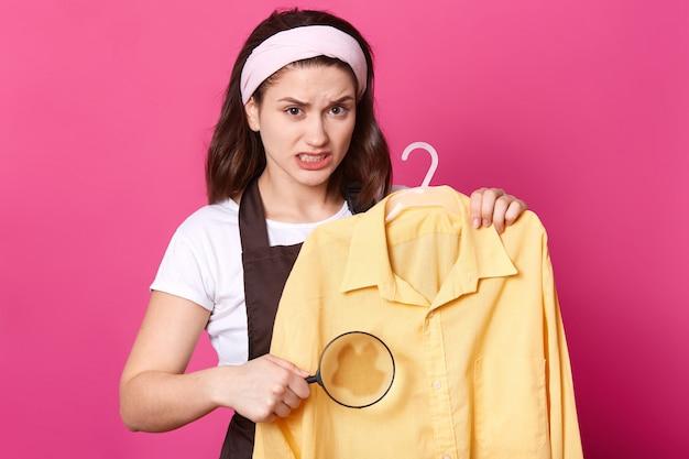Portret van geërgerde verstoorde vrouw die met geel overhemd op hanger loopt, loupe houdt, vlek groter maakt, geïrriteerd met vuil op kleren, met teleurgestelde gezichtsuitdrukking. huis klusjes concept.