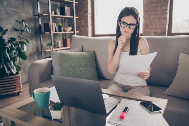 Portret van gefocust minded girl sit divan werk lees docs
