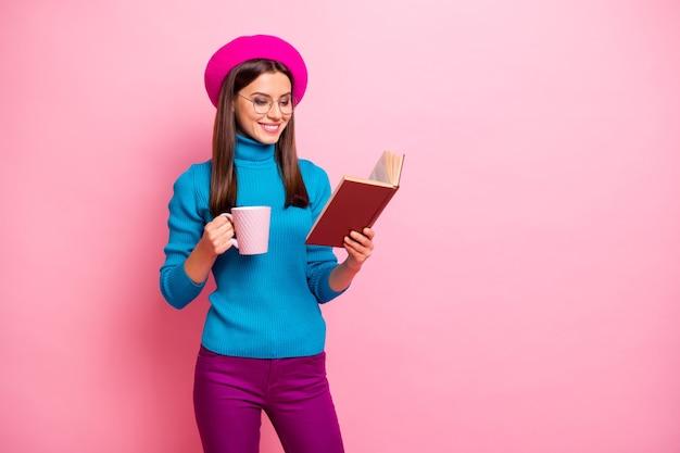 Portret van gefocust vrolijk meisje hebben weekends gelezen leerboek houden warme drank mok draag paarse broek.