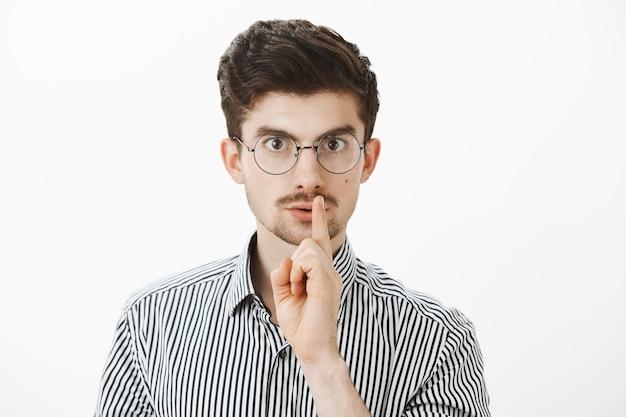 Portret van gefocuste serieuze nerdy kerel in ronde bril, shh zegt terwijl hij een zwijggebaar maakt met wijsvinger voor de mond, nerveuze vriend voelt geheim zal vertellen