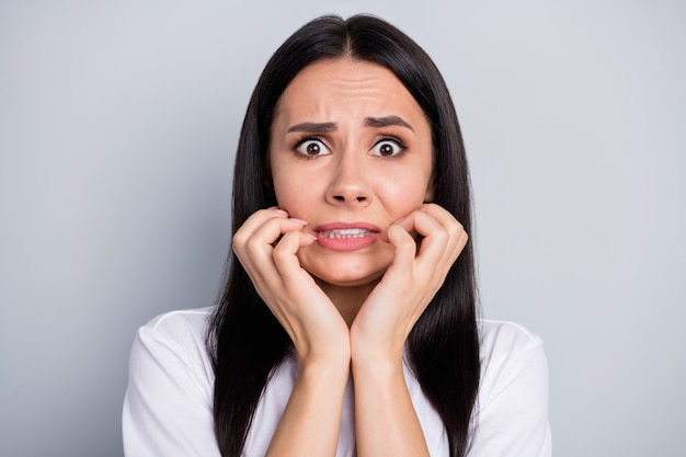 Portret van gefrustreerd angstig wanhoop meisje hoor vreselijke covid19 infectie nieuwigheid onder de indruk bijten tanden vinger voelen angst dragen witte trendy kleding geïsoleerd over grijze kleur achtergrond