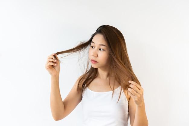 Portret van gefrustreerde jonge aziatische brunette vrouw met geknoeid haar op witte ondergrond. detailopname.
