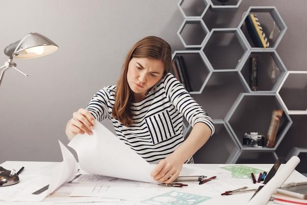 Portret van gefrustreerde jonge europese donkerharige freelancemanager die op telefoon met teamleider spreekt, die fout in projectblauwdrukken probeert te vinden. freelance, teamwerk concept