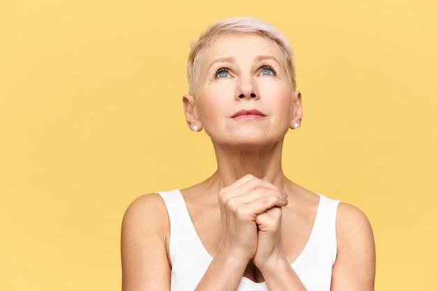 Portret van gefrustreerde nerveuze vrouw van middelbare leeftijd met kort blond haar opzoeken en hand in hand, met hoopvolle gezichtsuitdrukking, biddend tot god, vragen om haar te helpen door moeilijke tijden heen