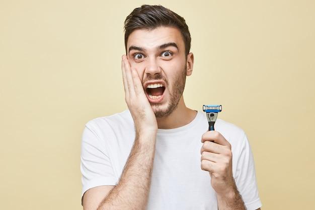 Portret van gefrustreerde ongelukkige jonge europese man met stoppels die hand op zijn wang vasthoudt en schreeuwt, met een terriified blik, last heeft van huidirritatie vanwege het scheren, met een scheermesje