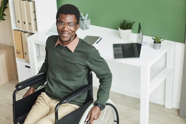 Portret van gehandicapte afrikaanse zakenman zittend op een rolstoel in de buurt van zijn werkplek en glimlachen