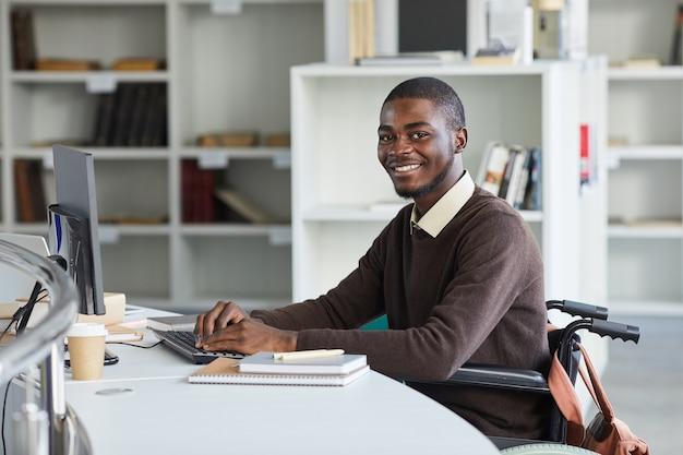 Portret van gehandicapte afro-amerikaanse man met behulp van computer en glimlachend in de camera tijdens het studeren in de universiteitsbibliotheek,