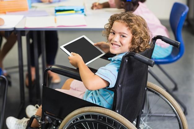 Portret van gehandicapte schooljongen die digitale tablet gebruiken