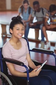 Portret van gehandicapte schoolmeisje met behulp van digitale tablet met klasgenoten op achtergrond
