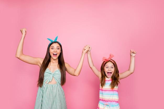 Portret van geïmponeerde meisjes die hun vuisten opheffen, handen schreeuwen wow omg het dragen van hoofdbanden levensstijl rok jurk geïsoleerd op roze achtergrond