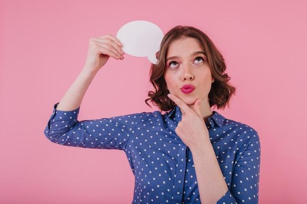 Portret van geïnspireerde krullende vrouw die over iets interessants denkt. binnen schot van vrolijk meisje in blauw shirt haar kin aan te raken en op te zoeken.
