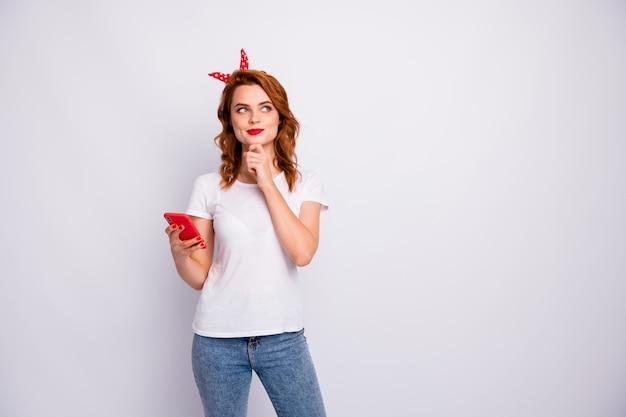 Portret van geïnteresseerd mooi meisje gebruik slimme telefoon denk gedachten willen blog sociale media posten slijtage jeans t-shirt geïsoleerd over witte kleur muur