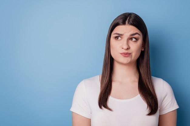 Portret van geïnteresseerde onzekere dame kijkt lege ruimte twijfels op blauwe achtergrond