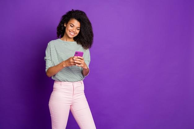 Portret van geïnteresseerde schattige zoete afro-amerikaan gebruikt haar mobiel