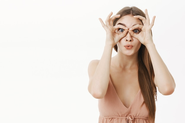 Portret van geïntrigeerde en tevreden elegante jonge vrouw in beige jurk die cirkels over ogen maakt alsof ze door een verrekijker kijkt naar grote verkopen, onder de indruk