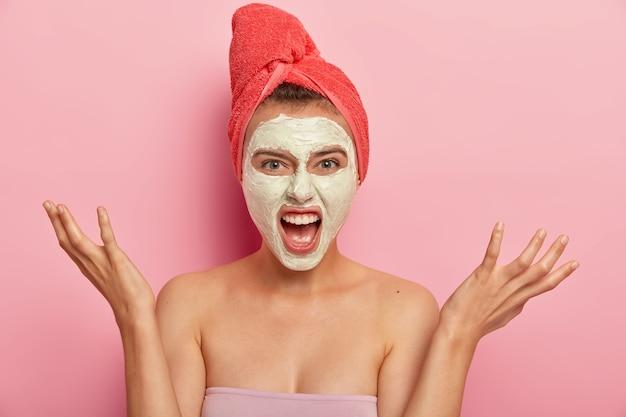 Portret van geïrriteerd vrouwelijk model schreeuwt van ergernis, heeft schoonheidsbehandelingen, heft handpalmen op, gebaart boos, past voedend kleimasker toe op gezicht, draagt badhanddoek op hoofd, geïsoleerd op roze muur
