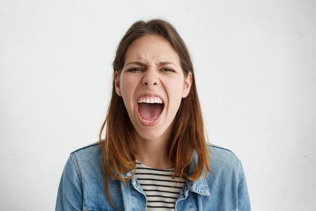 Portret van geïrriteerde boze vrouw met sluik donker haar fronsen haar gezicht wijd open mond uiten haar ontevredenheid.