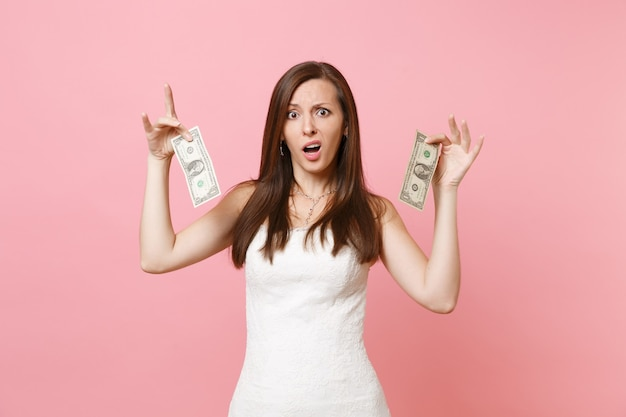 Portret van geïrriteerde droevige vrouw in witte kanten jurk met biljetten van één dollar