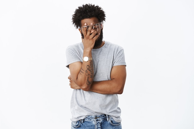 Portret van geïrriteerde en geërgerde vermoeide afro-amerikaanse man die zich schaamt met dronken vriend die een facepalmgebaar maakt met de hand op het gezicht, ogen sluiten van ergernis