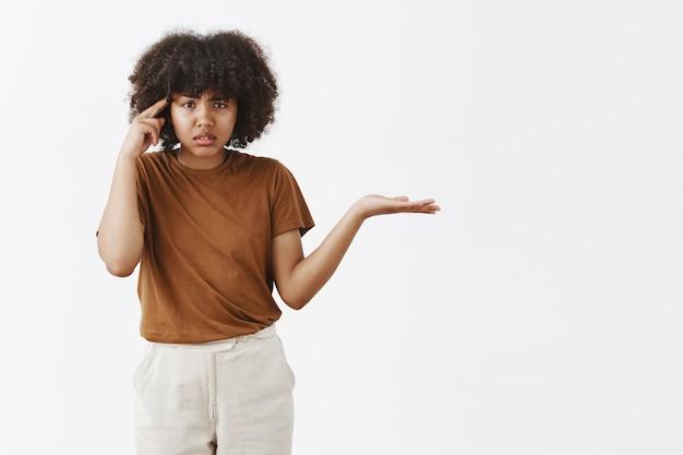 Portret van geïrriteerde en pissige ondervraagde afro-amerikaanse vrouw met afro kapsel schouderophalend met gespreide palm en rollende wijsvinger in de buurt van tempel iemand schelden
