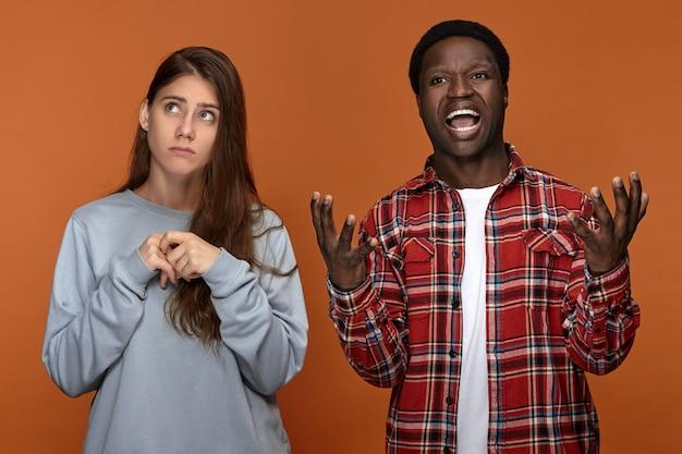 Portret van geïrriteerde, gekke jonge donkere man die emotioneel gebaart en schreeuwt, boos is op zijn blanke vrouw die geen beslissing of keuze kan maken, opkijkt met een onzekere uitdrukking