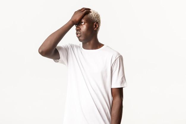 Portret van geïrriteerde knappe afro-amerikaanse blonde man, gezichtspalm en rologen gehinderd, klap voorhoofd ontevreden