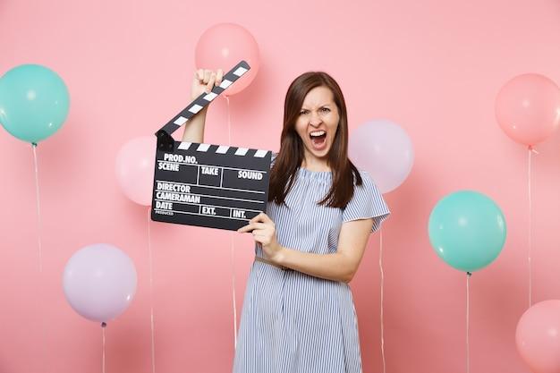 Portret van geïrriteerde ontevreden vrouw in blauwe jurk schreeuw houdt klassieke zwarte film filmklapper op roze achtergrond met kleurrijke luchtballonnen. verjaardagsfeestje, oprechte emoties van mensen.
