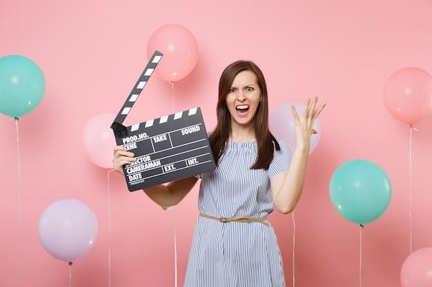 Portret van geïrriteerde vrouw in blauwe jurk die handen uitspreidt met klassieke zwarte film die filmklapper maakt op roze achtergrond met kleurrijke luchtballonnen. verjaardagsfeestje, oprechte emoties van mensen.